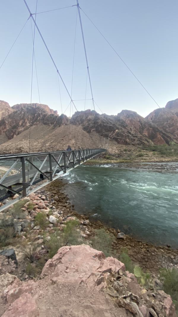 Backpackers cross the bridge over the Colorado River