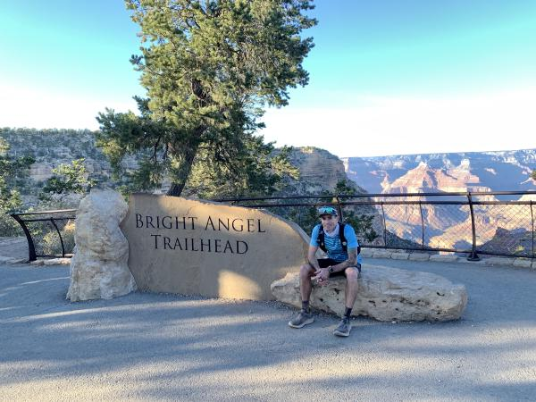 Chris sits next to the Bright Angel trailhead sign, exhausted after finishing.