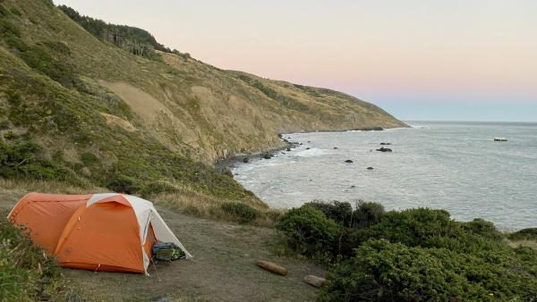 A tent perched on a seaside bluff