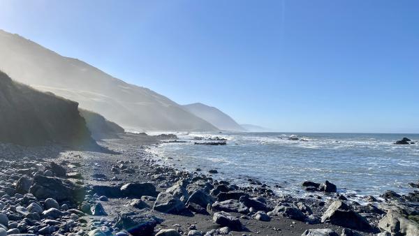 The morning sunlight starts to illuminate the rock-covered beach