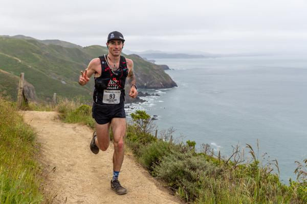 Chris smiles as he runs on coastal singletrack
