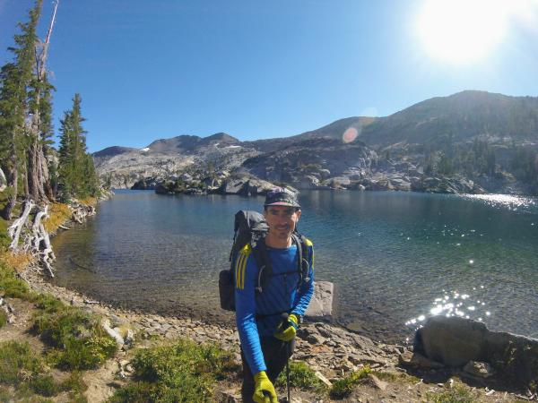 Chris in front of a clear mountain lake