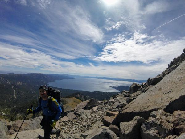 Chris hikes along a rocky mountainside, with Lake Tahoe in the background