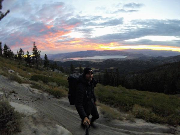 Chris on a mountainside trail, below a colorful sunrise