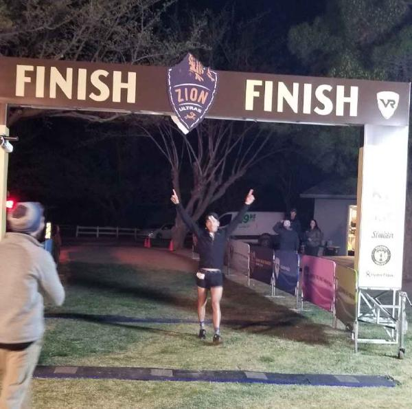 Chris runs across the finish line with his hands in the air